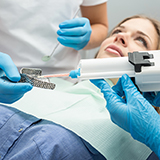 Woman in dentist chair recieving whitening treatment