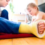 Image close up of little boy's broken leg in a cast plaing with his brother